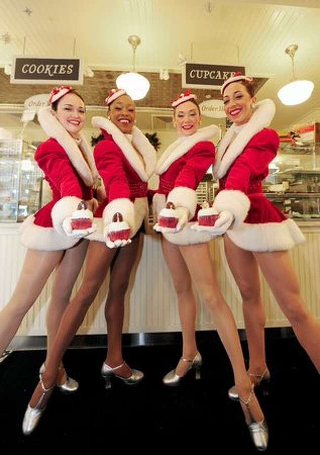 "Radio City Rockettes display ""Rockette Red Velvet"" cupcakes at Magnolia bakery in New York, Tuesday. The Rockettes unveiled, in partnership with Magnolia bakery, cupcakes with whipped vanilla buttercream icing and topped with edible chocolate disk, sketched with Rockettes. People buying a cupcake will receive special offer tickets for the Radio City Christmas Spectacular show which runs until January 03, 2010. Photo: Getty Images / Getty Images"