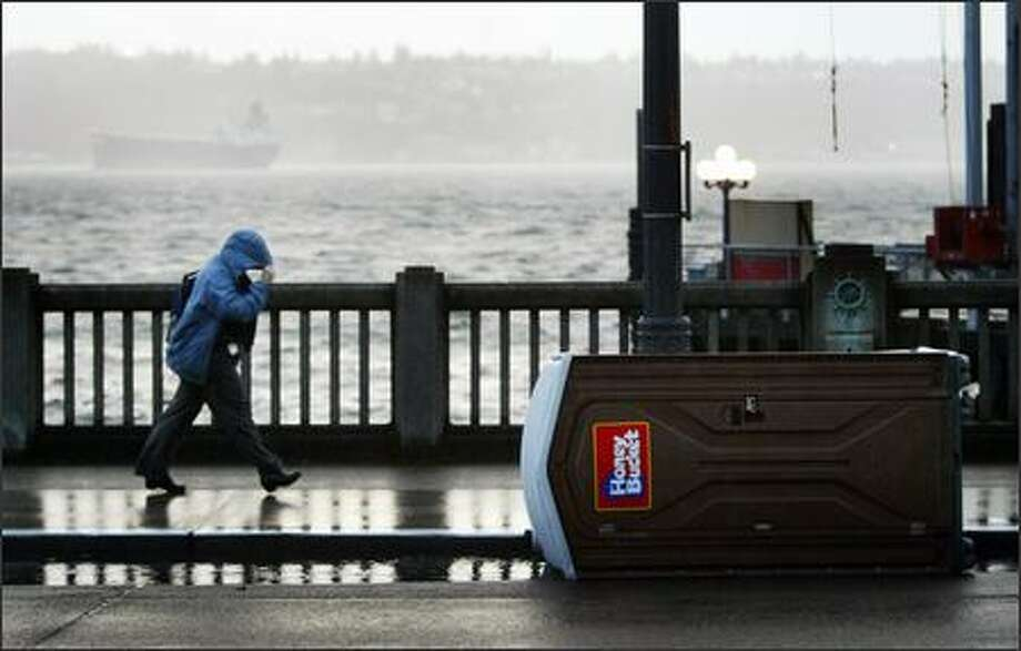 A pedestrian pushes through the wind on the Seattle waterfront on Monday. Photo: Joshua Trujillo, Seattlepi.com / seattlepi.com