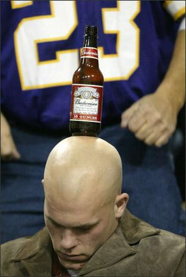 A sleepy Minnesota Vikings fan finds himself used as a pub table by friends as he dozes during the fourth quarter of the Vikings' game against the Seattle Seahawks at the Metrodome in Minneapolis. Seattle won 27-23. Photo: Mike Urban, Seattle Post-Intelligencer / Seattle Post-Intelligencer