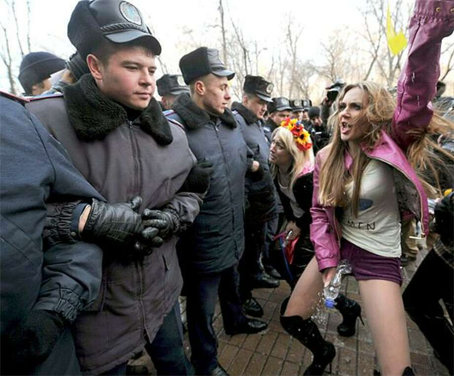 """You go girl:In Kiev, FEMEN activists pretend to urinate in front of Ukraine's Cabinet Ministers building because """"the Cabinet is a men's room."""" The feminists are unhappy with the lack of women in Prime Minister Mykola Azarov's newly reorganized government. Photo: Sergei Supinsky, AFP / Getty Images / AFP / Getty Images"""