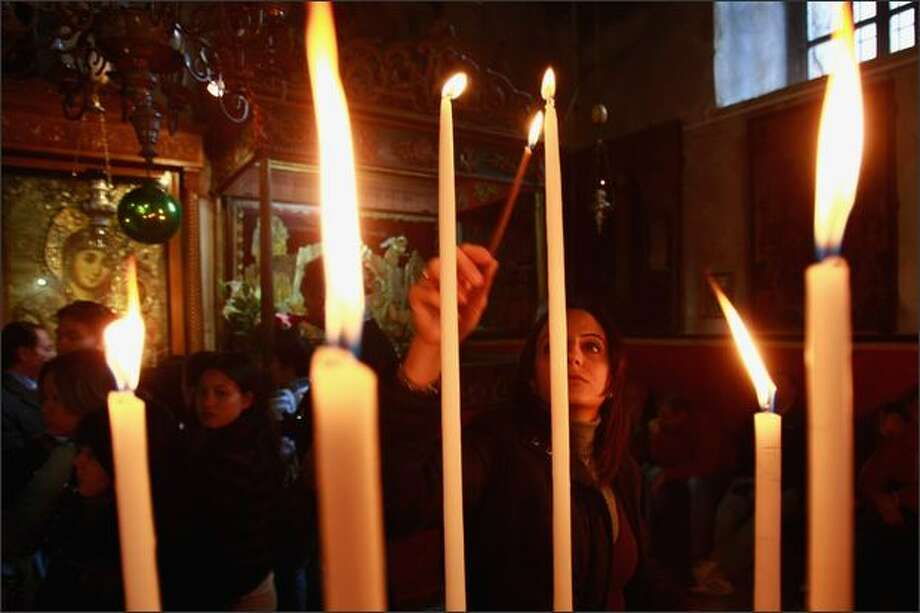 A worshiper lights candles at the entrance to the Grotto of the Church of the Nativity, the traditional birthplace of Jesus, on Sunday in the biblical town of Bethlehem in the West Bank. Just 10 days to go before Christmas, the city is bustling with tourists as Israeli and Palestinian forces are cooperating to make this the most cheerful Christmas since the second Palestinian Intifada broke out in September 2000. Photo: Getty Images / Getty Images