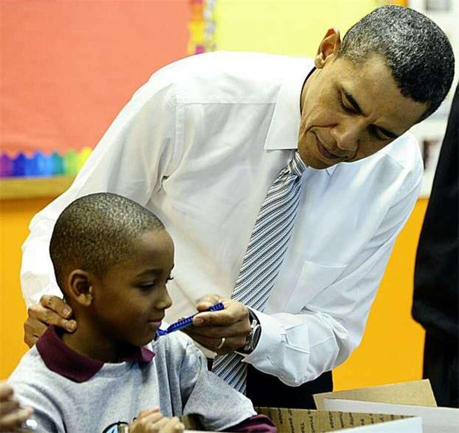 Shave the children: President Obama pretends to trim a boy's whiskers as he, the Los Angeles Lakers and community children pack gifts for troops and homeless people at a Boys and Girls Club in Washington. Photo: Jewel Samad, AFP / Getty Images / AFP / Getty Images