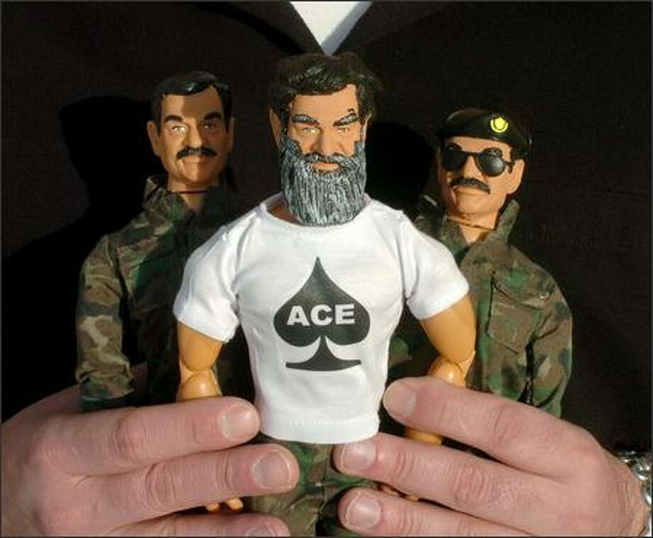 Emil Vicale, president of HeroBuilders.com in Danbury Conn., holds  dolls made by his company. The latest is the Captured Saddam, center, wearing a beard and a T-shirt with the ace of spades. The others are the Saddam Insane doll, left, and The Butcher of Baghdad doll. (AP Photo Douglas Healey) Photo: U.S. Coast Guard / U.S. Coast Guard