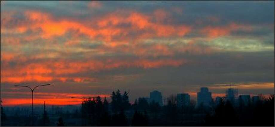 Bellevue's skyline forms a dark silhouette against the setting sun on Saturday.  Most of the city, and the Eastside, remained without power because of damage caused by Thursday's storm. Photo: Karen Ducey, Seattle Post-Intelligencer / Seattle Post-Intelligencer