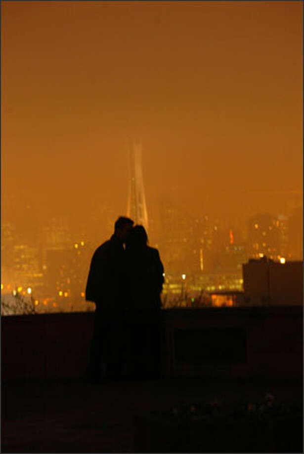 It was foggy Friday night as Eric Warren and Lei Castro stood on the southerly slope of Queen Anne Hill, looking out over the subdued lights of Seattle, a city that seemed to beckon with possibility and promise. They walked over to a bench in Kerry Park, and then Warren proposed to Castro. She said yes. Photo: Grant M. Haller, Seattle Post-Intelligencer / Seattle Post-Intelligencer