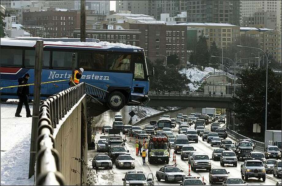 Two buses slide down E. Thomas St., one crashing through the guide rail and suspended over I-5, in Seattle on Friday. Photo: Dan DeLong, Seattle Post-Intelligencer / Seattle Post-Intelligencer