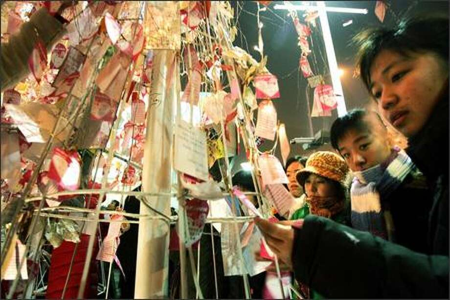 Chinese teenagers examine papers written with Christmas wishes tied to a Christmas tree outside a shopping mall on the eve to Christmas in Beijing, China. Christmas is gaining popularity among young Chinese as businesses take advantage of the gift giving tradition to boost their end of year sale. (AP Photo/Ng Han Guan) Photo: Seattle Post-Intelligencer / Seattle Post-Intelligencer