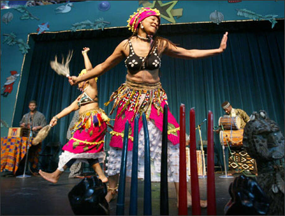 The Seattle Center marked the first day of Kwanzaa on Monday with a performance by the Seattle-based Adefua African Music and Dance Company. In the foreground is dancer Komala Martin. The candles represent each of the seven days of the weeklong celebration of African culture. Photo: Paul Joseph Brown, Seattle Post-Intelligencer / Seattle Post-Intelligencer