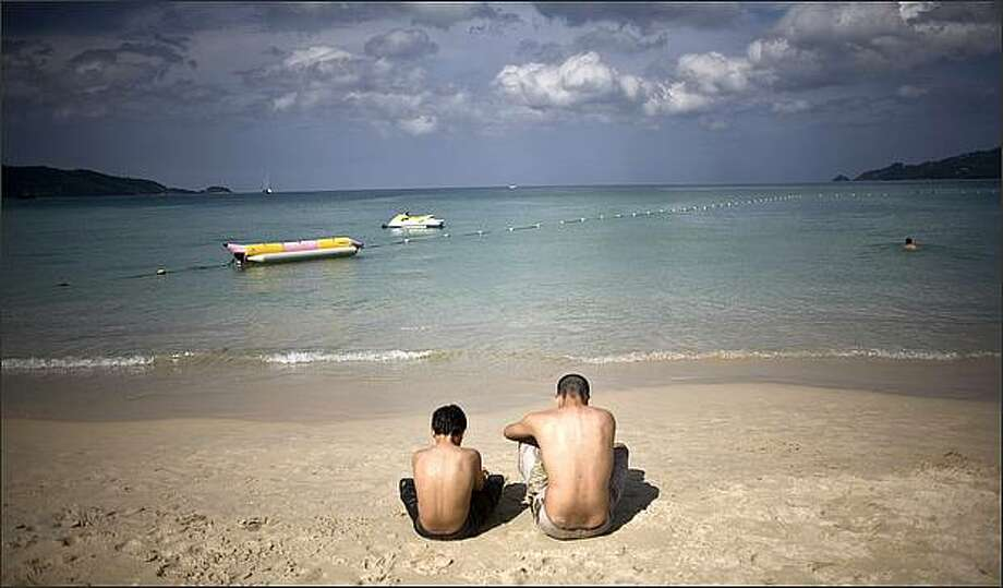 Two unidentified western tourists spend a quiet moment on Patong Beach Phuket, Thailand on the fourth anniversary of the 2004 Indian Ocean tsunami. (AP Photo/David Longstreath)