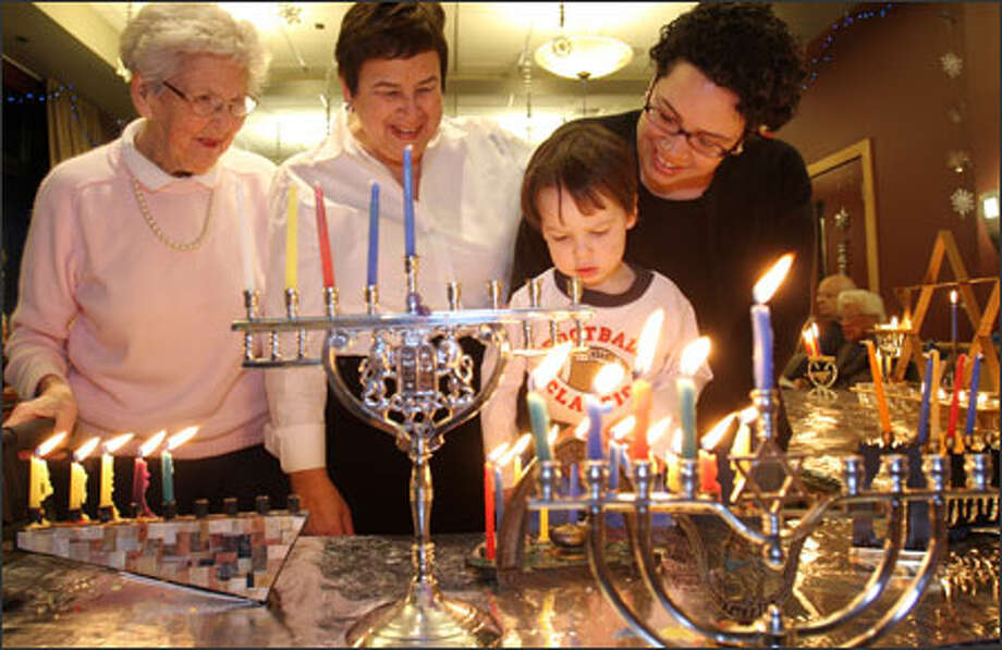 Four generations of Seattleites light Hanukkah candles Wednesday on the fourth night of the celebration at The Summit at First Hill. They are, from left: Shirley Berch, 89, who lives at The Summit; Gena Gorasht, her daughter; Jamie Holland, Gorasht's daughter; and Holland's son, Samuel Holland, 2. Photo: Meryl Schenker, Seattle Post-Intelligencer / Seattle Post-Intelligencer