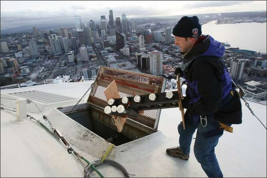 Scott Streeper of Pyro Spectaculars installs fireworks atop the Space Needle on Sunday in preparation for Seattle's New Year's Eve celebrations. The eight-minute display set to music will feature several thousand pyrotechnic shots, according to a news release. Photo: Karen Ducey, Seattle Post-Intelligencer / Seattle Post-Intelligencer