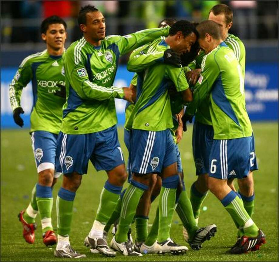 Sounders players surround Steve Zakuani after he scored a goal in the first half. Photo: Joshua Trujillo, Seattlepi.com / seattlepi.com