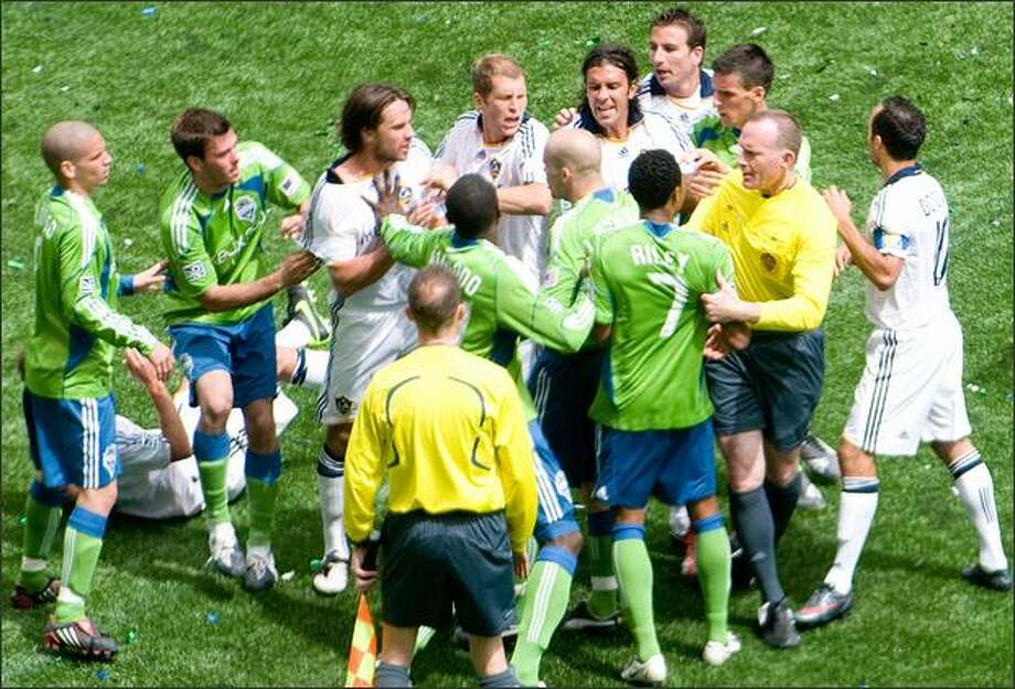 Seattle Sounders' James Riley (7) is pulled away by referee Tim Weyland and given a red-card ejection in the 56th minute after he hit an L.A. Galaxy player in their 1-1 draw game at Qwest Field. Photo: Daniel Berman, Seattlepi.com / Seattlepi.com