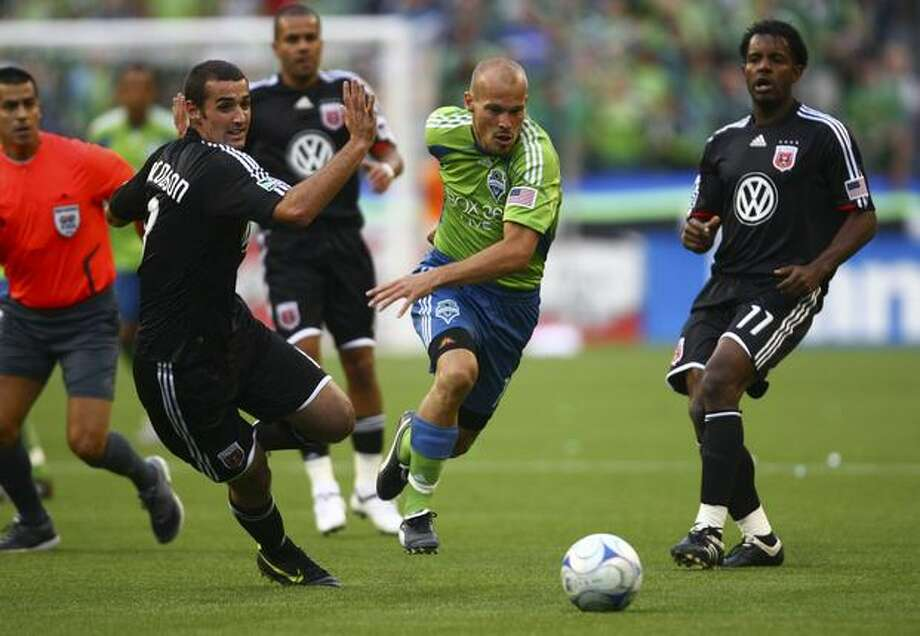 Seattle Sounders' Freddie Ljungberg powers past D.C. United's Andrew Jacobson, left, and Luciano Emilio (11) during the first half. Photo: Joshua Trujillo, Seattlepi.com / seattlepi.com