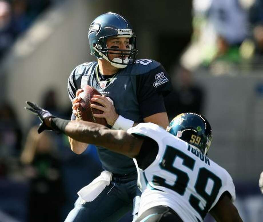Quarterback Matt Hasselbeck #8 of the Seattle Seahawks drops back to pass under pressure from Brian Iwuh #59 of the Jacksonville Jaguars. Photo: Getty Images / Getty Images