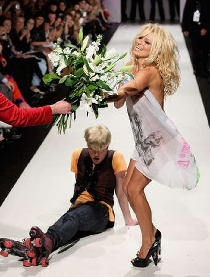 Pamela Anderson and Richie Rich walk the catwalk following the A Muse by Richie Rich collection show on day four of Air New Zealand Fashion Week. Photo: Getty Images / Getty Images