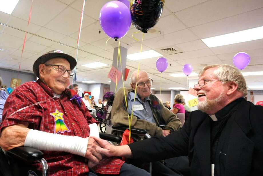 Father Paul Merry, right, signs happy birthday to Rolf Haferl, 106, left,  and Frank Euvrard, 101, center, during a party at Pope John Paul II Care and Rehabilitation Center in Danbury on Thursday, Sept 24, 2009. Photo: Michael Duffy / The News-Times