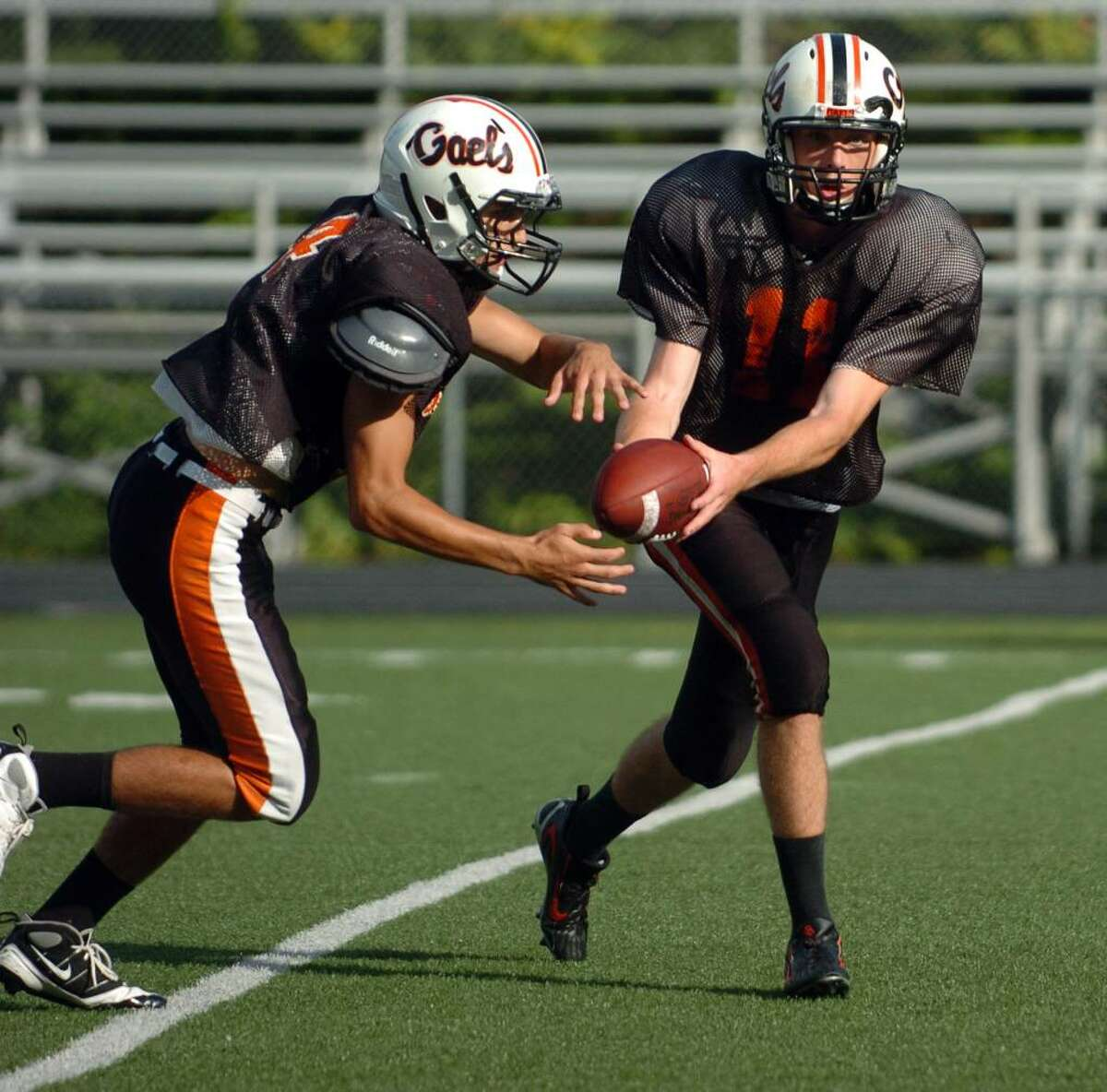 Shelton QB Ryan Pendagast, right, hands off the ball to running back Joel Youd during team practice in Shelton, Conn. on Wednesday Sept. 23, 2009.