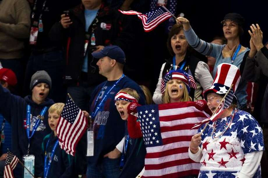 USA Fans cheer the USA's Apolo Anton Ohno competes in the men's 1000 meters in short track speed skating at the 2010 Winter Olympics on Saturday, Feb. 20, 2010, in Vancouver. With a bronze medal in the event, Ohno became the most decorated American winter athlete, collecting his seventh medal. ( Smiley N. Pool / Houston Chronicle). Photo: Hearst Newspapers / Hearst Newspapers