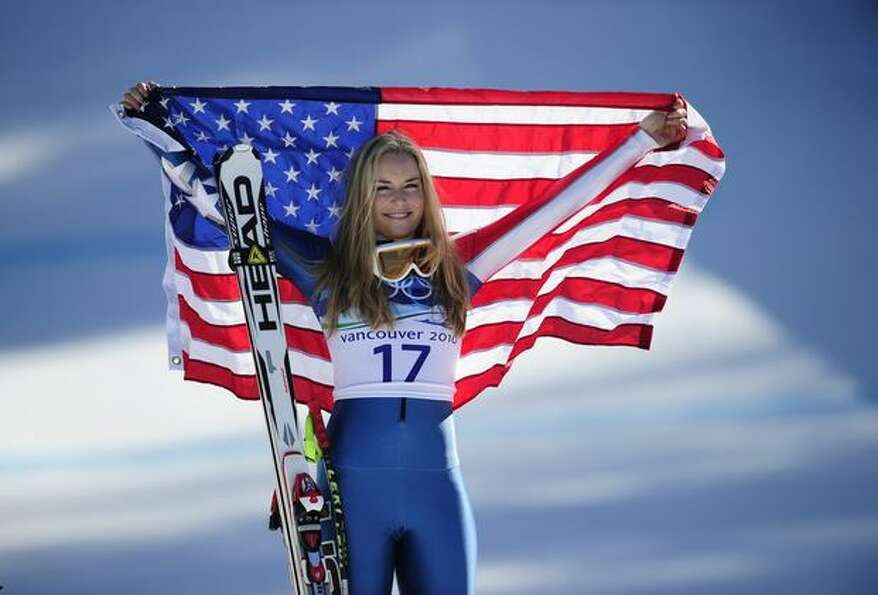 USA's bronze medalist Lindsey Vonn celebrates with her national flag on the podium during the flower