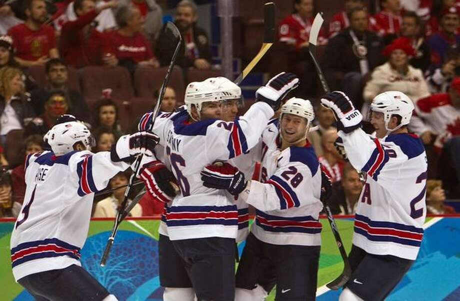USA's Brian Rafalski (28) is mobbed by teammates after scoring early in the first period against Canada in men's hockey preliminary round action at the 2010 Winter Olympics in Vancouver on Sunday, Feb. 21, 2010. (Smiley N. Pool/Houston Chronicle) Photo: Hearst Newspapers / Hearst Newspapers