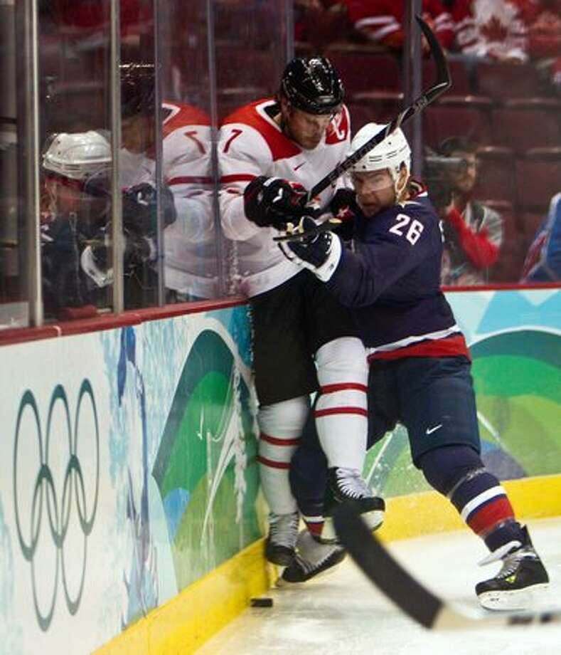 USA's Paul Stastny checks Switzerland's Mark Streit during the first period in men's hockey quarterfinal action at the 2010 Winter Olympics on Wednesday, Feb. 24, 2010, in Vancouver. (Smiley N. Pool / Houston Chronicle) Photo: Smiley N. Pool, Hearst Newspapers / Hearst Newspapers