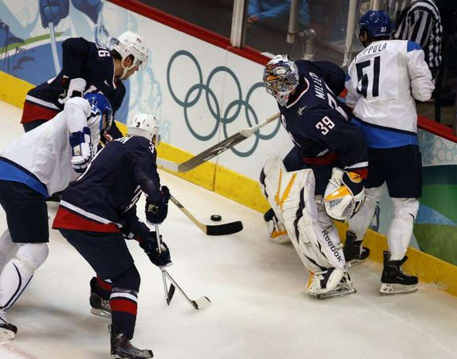 Goalie Ryan Miller found himself in the thick of the action behind his net in the first period of the United States vs. Finland semifinal hockey game at the Winter Olympic Games in Vancouver, British Columbia, on Thursday, Feb. 25, 2010..Paul Chinn/Chronicle Olympic Bureau Photo: Paul Chinn, Hearst Newspapers / Hearst Newspapers