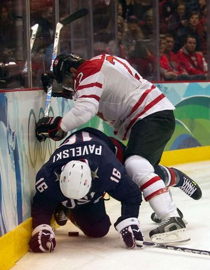 USA's Joe Pavelski is pushed to the ice by Canada's Dan Boyle during the men's ice hockey gold medal game at the 2010 Winter Olympics in Vancouver, B.C., on Sunday, Feb. 28, 2010. (Smiley N. Pool / Houston Chronicle) Photo: Hearst Newspapers / Hearst Newspapers