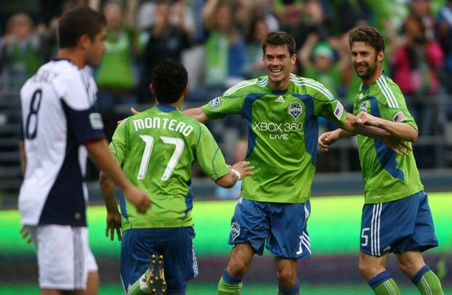 Seattle Sounders players Fredy Montero (17), Brad Evans (3) and Pat Noonan (25) celebrate a goal by teammate Steve Zakuani against the New England Revolution in the first half of an MLS soccer match on June 5, 2010 at Qwest Field in Seattle. (Photo by Joshua Trujillo, Seattlepi.com). Photo: Joshua Trujillo, Seattlepi.com / seattlepi.com
