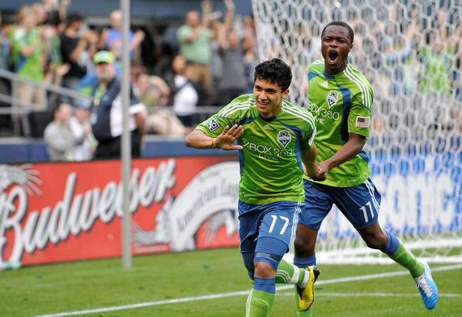 Fredy Montero celebrates his goal in the 14th minute with Steve Zakuani during July 6th game against FC Dallas. Photo: Sang Cho, Seattlepi.com / seattlepi.com