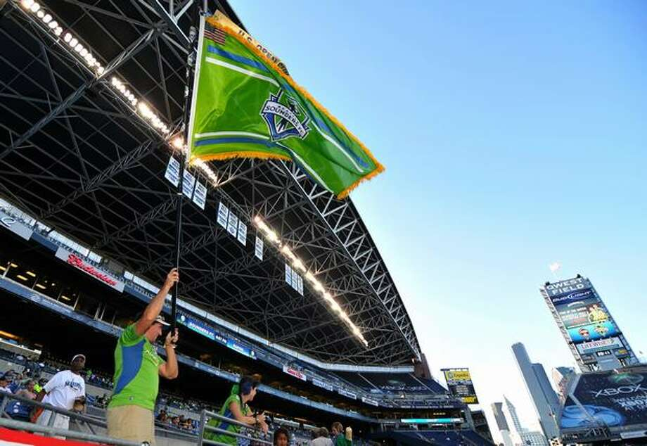 Sounders fan Steven Ward waves his autographed Sounders FC flag before the match against the Colorado Rapids. Photo: Sang Cho, Seattlepi.com / seattlepi.com