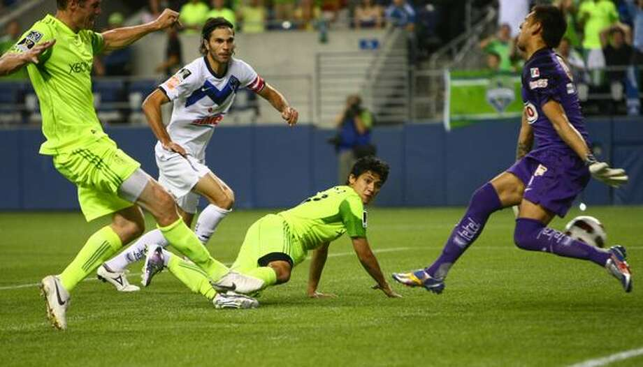 Seattle Sounders player Nate Jaqua gets the ball past C.F. Monterrey goalie Jonathan Orozco in the second half while Sounder Fredy Montero and Monterrey player Jose Maria Basanta watch the action during a CONCACAF Champions League match at Qwest Field in Seattle. The Sounders were called for an offsides penalty and the goal did not count. Photo: Joshua Trujillo, Seattlepi.com / seattlepi.com