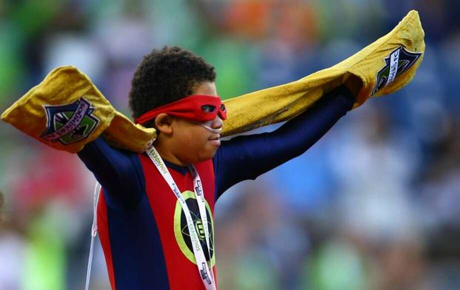 Seattle's own superhero, Electron Boy, aka Erik Martin, raises the golden scarf before an MLS match between the Seattle Sounders and Chicago Fire on Saturday August 28, 2010 at Qwest Field in Seattle. Martin, who has cancer, raised the scarf in front of thousands of cheering fans. Martin was recently honored as a super hero for a day by the Make-A-Wish Foundation. Photo: Joshua Trujillo, Seattlepi.com / seattlepi.com