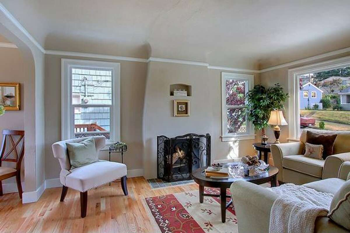 The living room has a fireplace, large windows and hardwood floors. (Windermere.com) See the listing.
