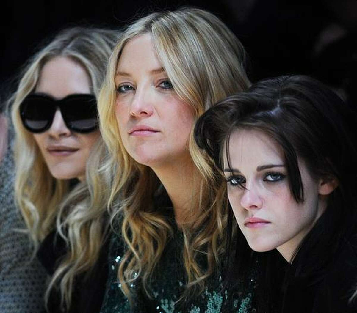 Actresses Mary-Kate Olsen, (L) Kate Hudson (C) and Kristen Stewart (R) watch the Burberry Womenswear fashion show for the Autumn/Winter 2010 collection on the fifth day of the London Fashion Week.