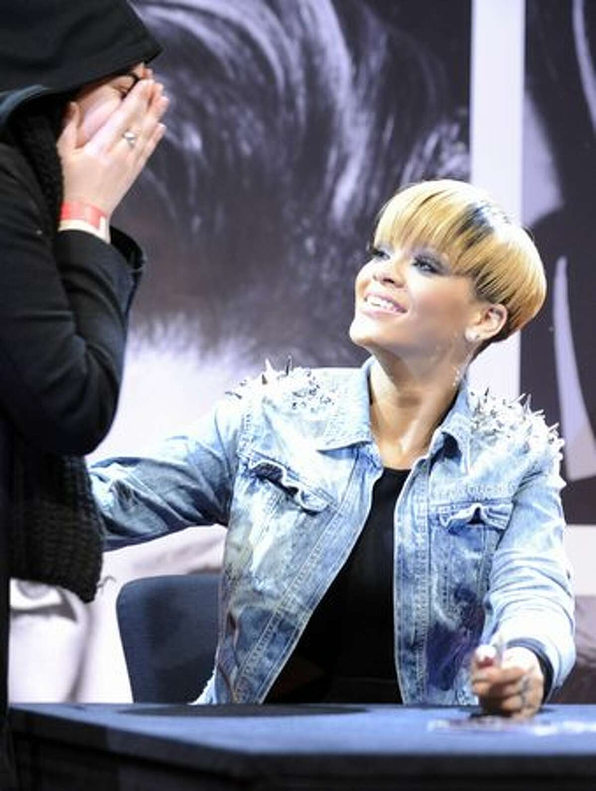 US singer Rihanna comforts a fan who cries as she receives an autograph at a shopping centre in Berlin.
