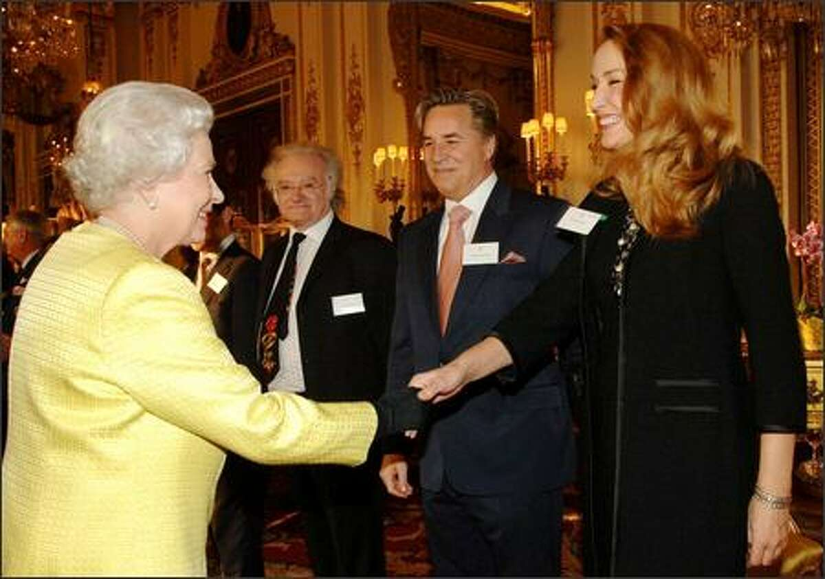Britain's Queen Elizabeth II shakes hands with model and actress Jerry Hall, watched by actor Don Johnson, during a reception at Buckingham Palace in London, Tuesday, for Americans based in Britain. On show was an exhibition devoted to photographs of the Queen with the American Presidents she has encountered. There have been 11 Presidents in power during her reign so far and the Queen has met all of them. Man second from left is unidentified. (AP Photo/Fiona Hanson, pool)