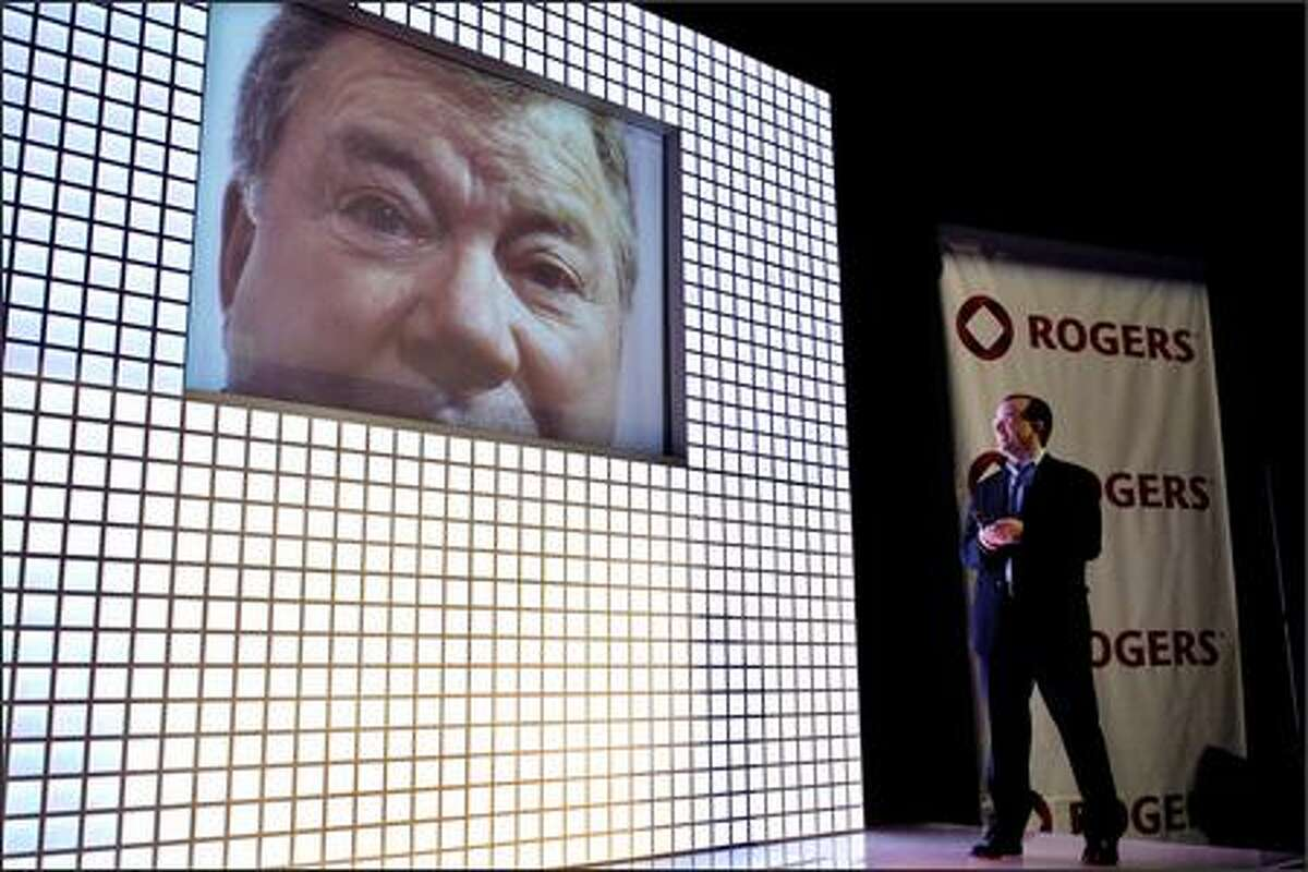Actor William Shatner is displayed on a monitor as Rogers Wireless Senior Vice President and Chief Marketing Officer John Boynton demonstrates wireless video calling at an unveiling event in Toronto, Monday. (AP Photo/CP, Aaron Harris)