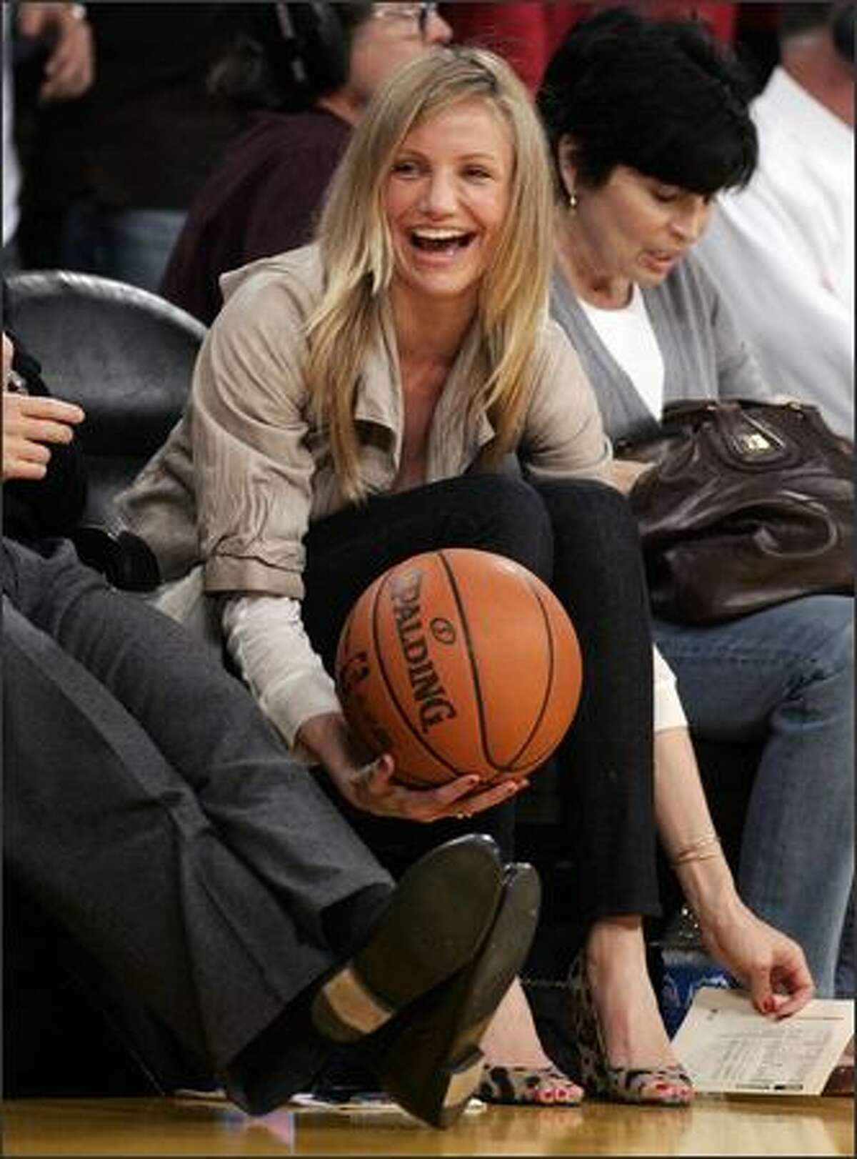Actress Cameron Diaz catches a basketball as she sits courtside during Game 2 of the NBA Western Conference semi-final basketball playoff game between the Houston Rockets and the Los Angeles Lakers in Los Angeles. (REUTERS/Danny Moloshok)
