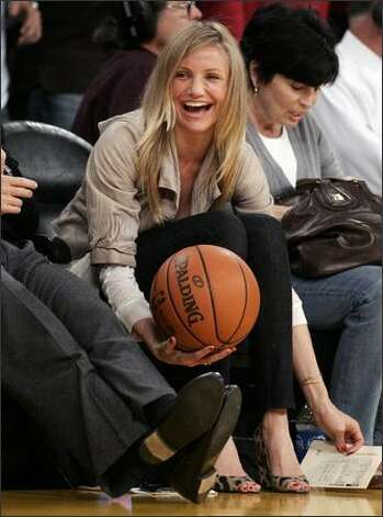 Actress Cameron Diaz catches a basketball as she sits courtside during Game 2 of the NBA Western Conference semi-final basketball playoff game between the Houston Rockets and the Los Angeles Lakers in Los Angeles. (REUTERS/Danny Moloshok) Photo: Getty Images / Getty Images