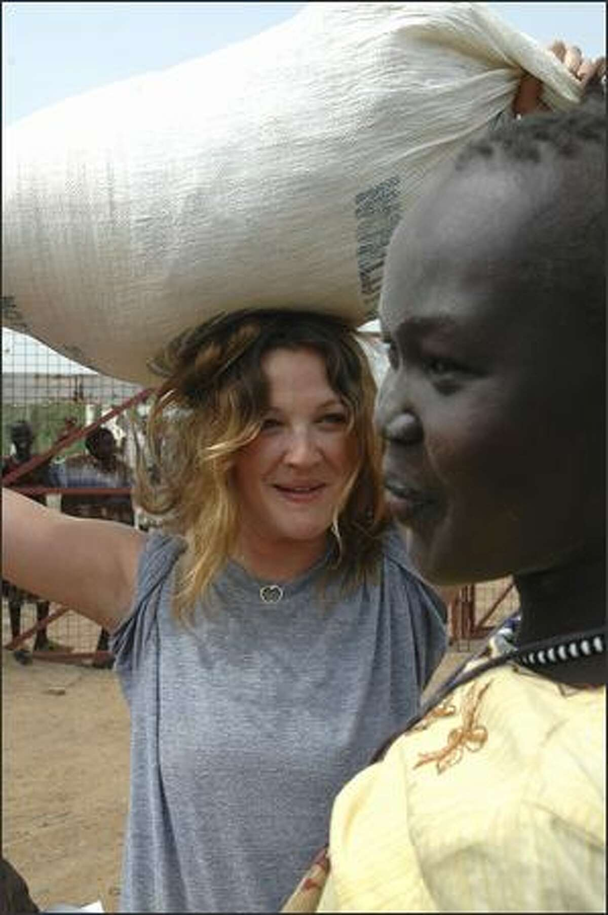 WFP ambassador against hunger actress Drew Barrymore hefts a heavy sack of food onto her head, the way many refugees would carry it home, in Kakuma, Kenya. (AP Photo/WFP, Guillaume Bonn)