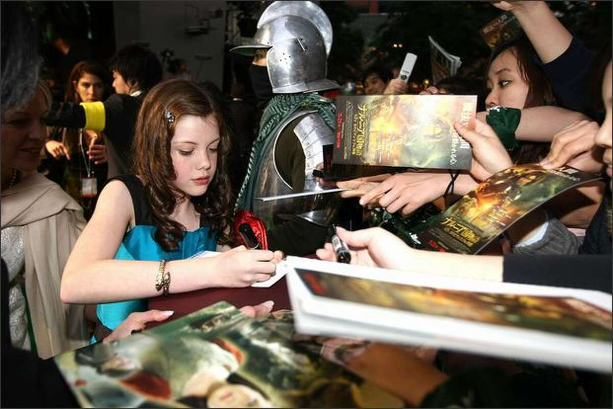 Actress Georgie Henley signs autographs for her fans during