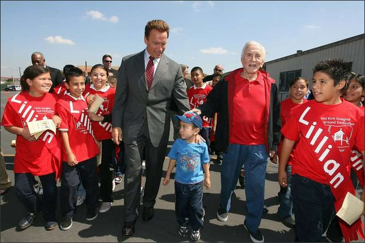 Actor Kirk Douglas (C-R) and governor of California Arnold Schwarzenegger (C-L) attend the Anne and Kirk Douglas 400th Playground Dedication at Lillian Street Elementary School in Los Angeles, California.