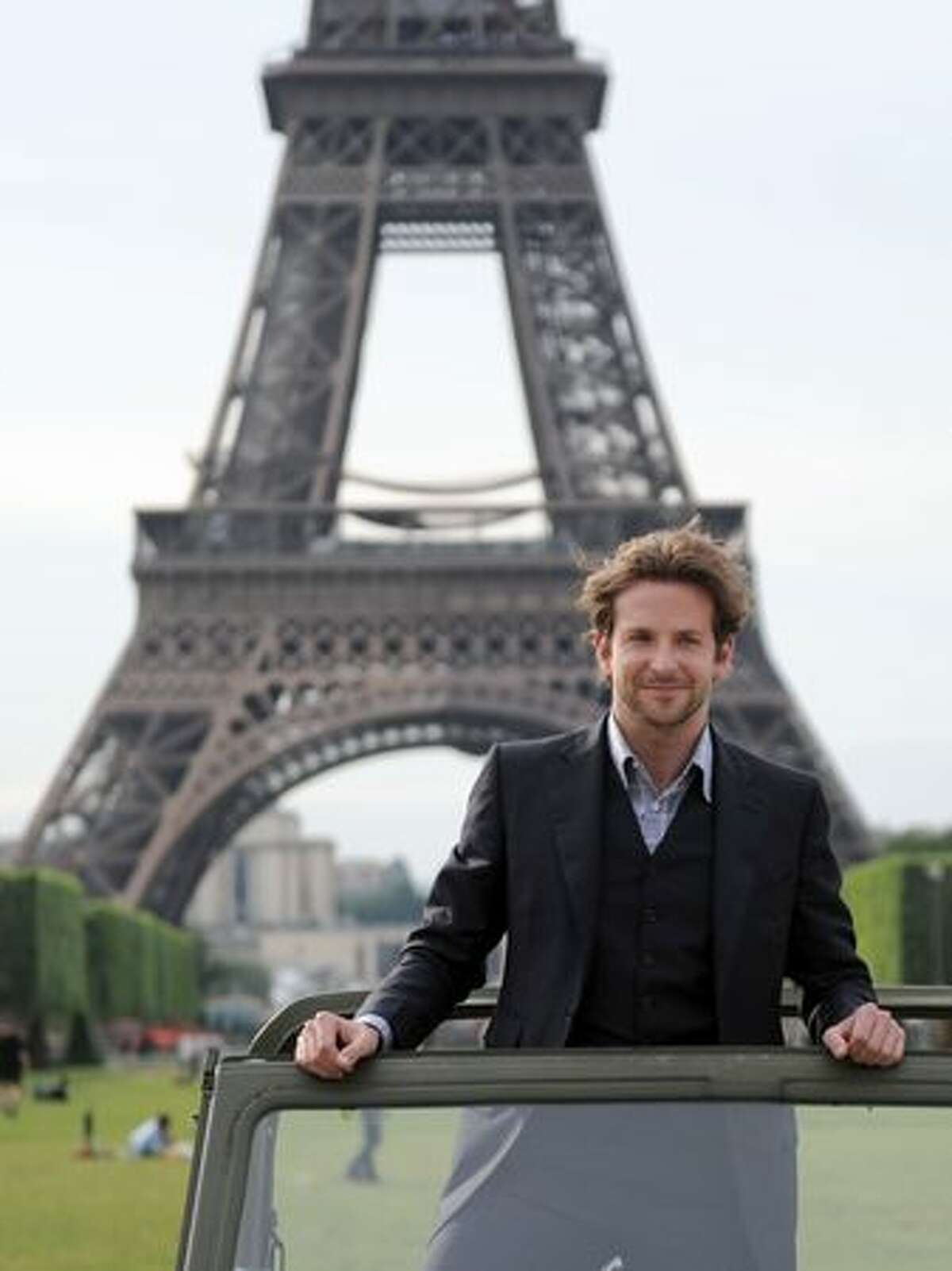 Actor Bradley Cooper poses in a car in front of the Eiffel Tower during a photocall for the release in France of the A-team film.