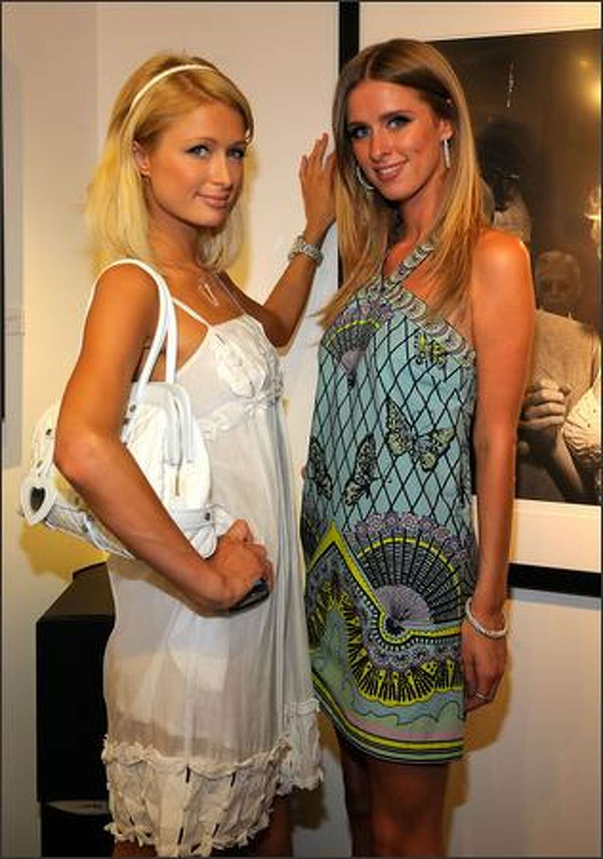 Socialites Paris Hilton (L) and Nicky Hilton attend the opening of