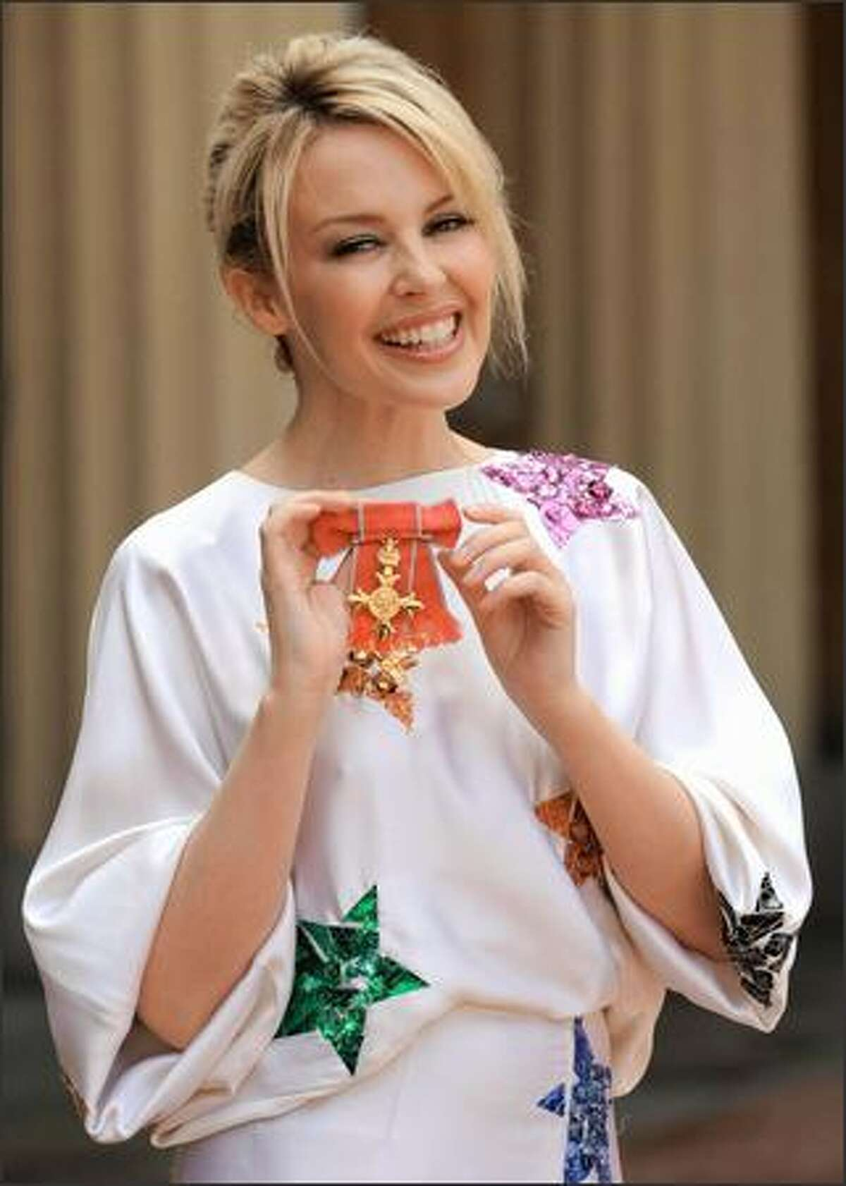 Australian pop singer Kylie Minogue poses for photographs after receiving her Order of the British Empire from the Prince of Wales for services to music at Buckingham Palace in London.