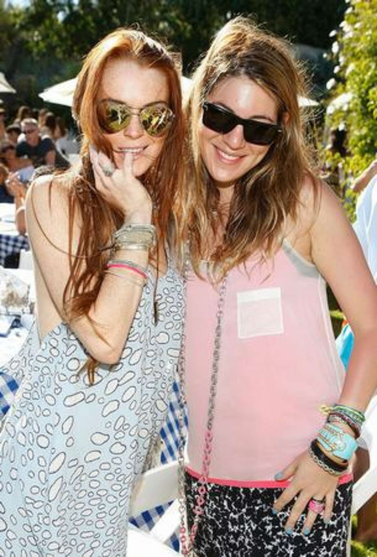 Actress Lindsay Lohan (L) and designer Dani Stahl attend the Lia Sophia Clam Bake at a private residence in Malibu, California.