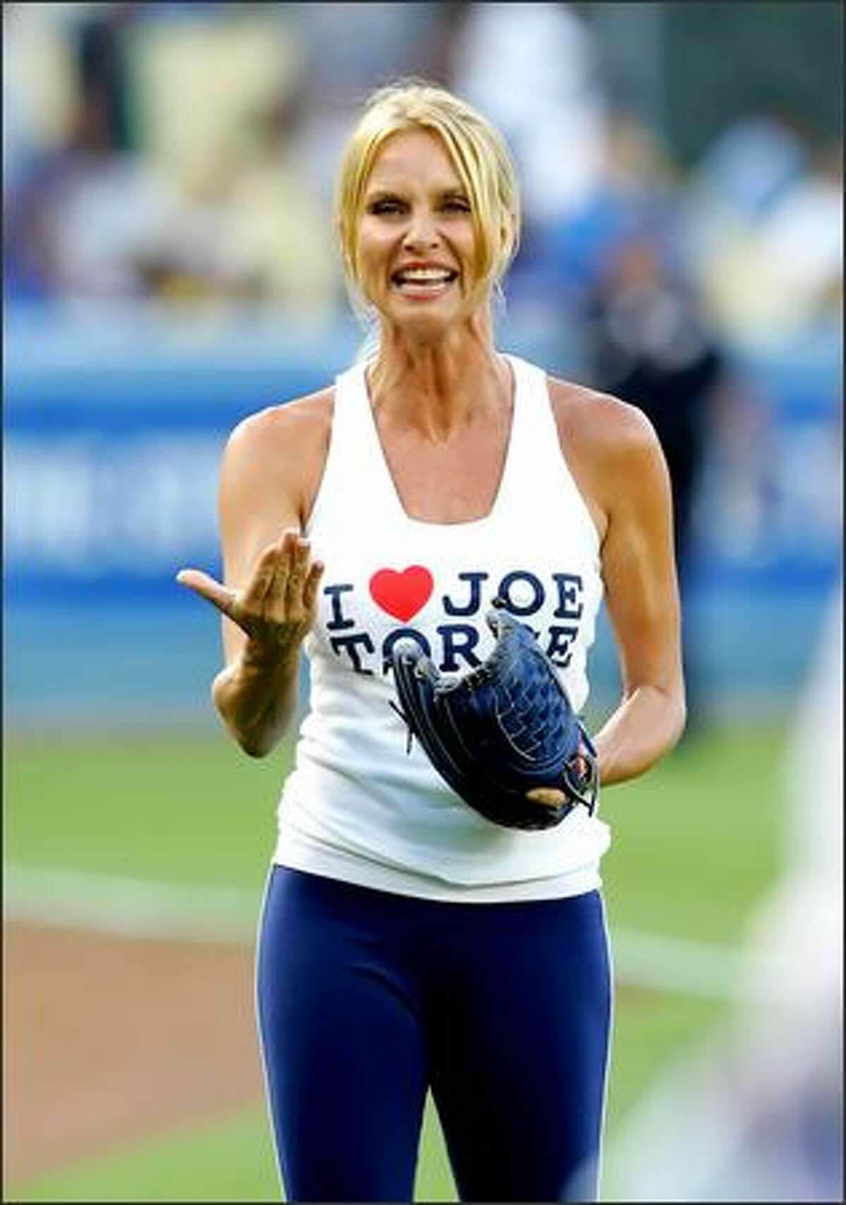 Actress Niccolite Sheridan walks along the field before throwing out the first pitch before the game between the San Francisco Giants and the Los Angeles Dodgers at Dodger Stadium in Los Angeles, California.
