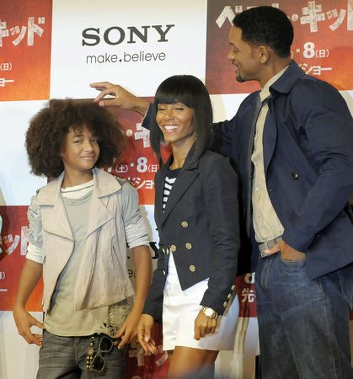"""Actor Will Smith (R) touches the hair of his son Jaden Smith while his wife Jada Pinkett Smith (C) smiles during a photo session and press conference for their latest movie """"Karate Kid"""" in Tokyo. Karate Kid, known as """"The Kung Fu Dream"""" in China and """"Best Kid"""" in Japan and South Korea, will open in cinemas across Japan on August 14."""