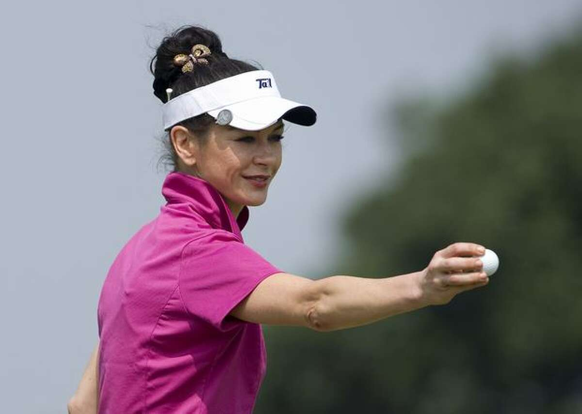Actress Catherine Zeta-Jones holds a ball on the 14th green during day three of the Mission Hills Start Trophy tournament at Mission Hills Resort in Haikou, China.